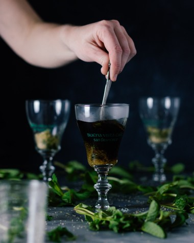 Vertical side shot of three Buena Vista Irish Coffee goblet glasses with a hand holding a spoon and stirring the coffee in the front glass.