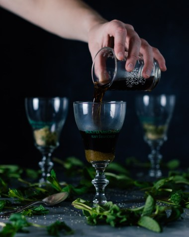 Vertical side shot of three Buena Vista Irish Coffee goblet glasses with a hand pouring coffee into the front glass.
