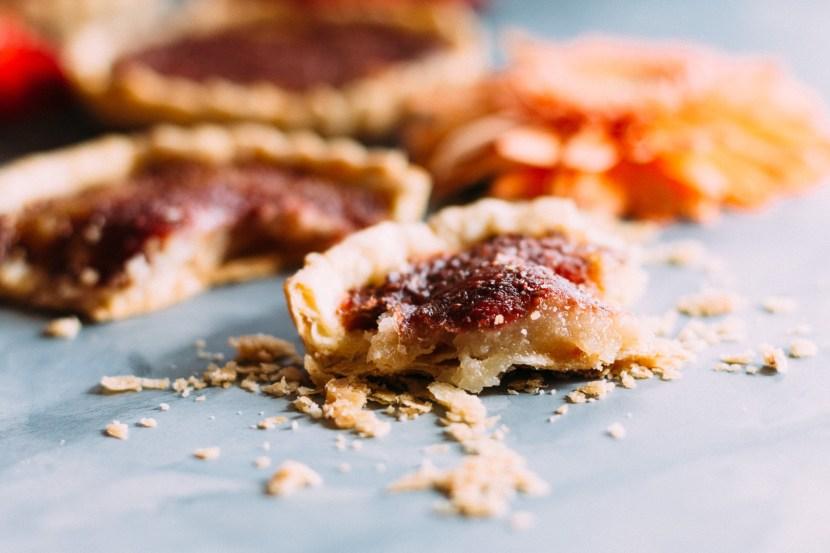Horizontal side shot of eaten tart showing the crust, marzipan, and jam layers.