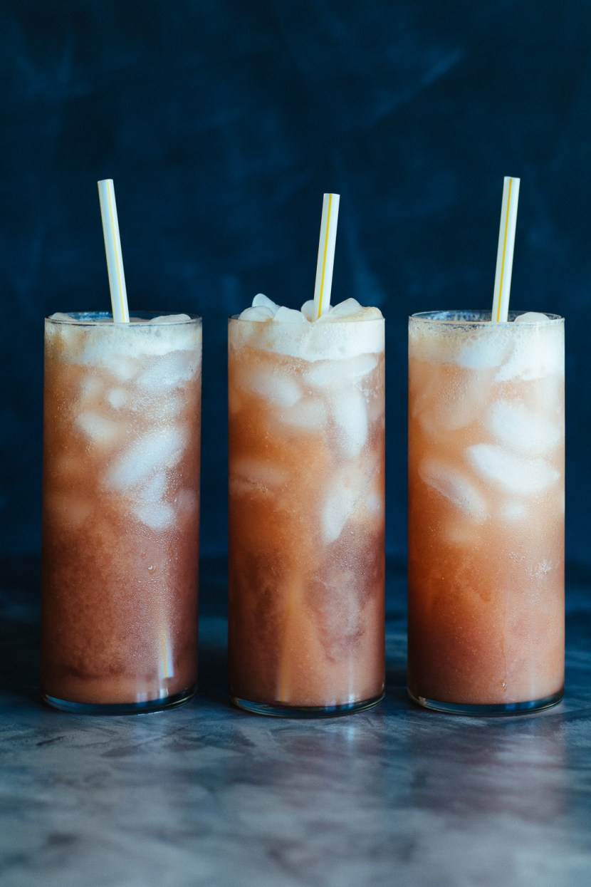 Vertical shot of three tall glasses filled with ice, straws, and Rhubarb Whiskey Collins.