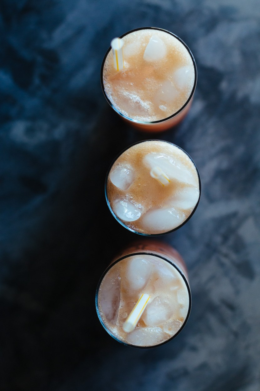 Overhead shot of three glasses lined up vertically filled with Rhubarb Whiskey Collins and straws.