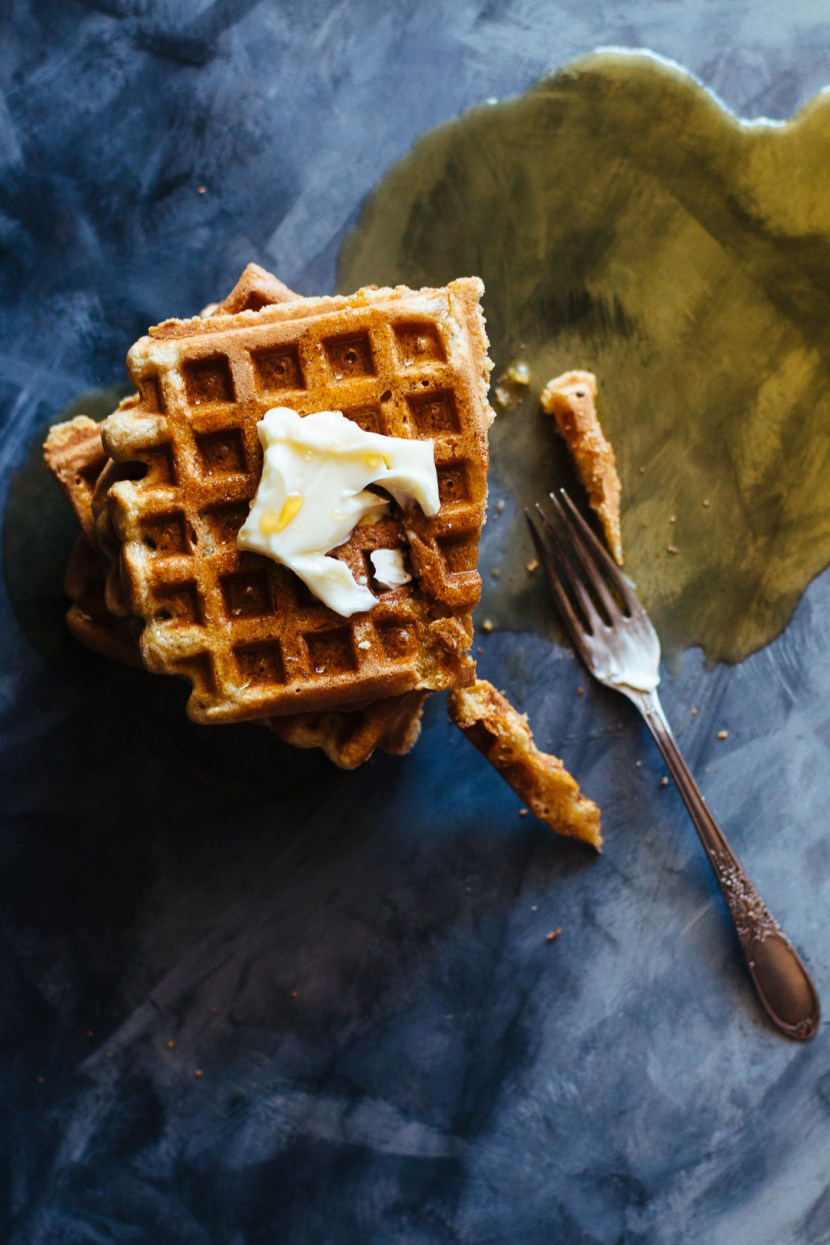 Overhead shot of a stack of waffles with a pat of butter on top, a fork, and a maple syrup puddle.