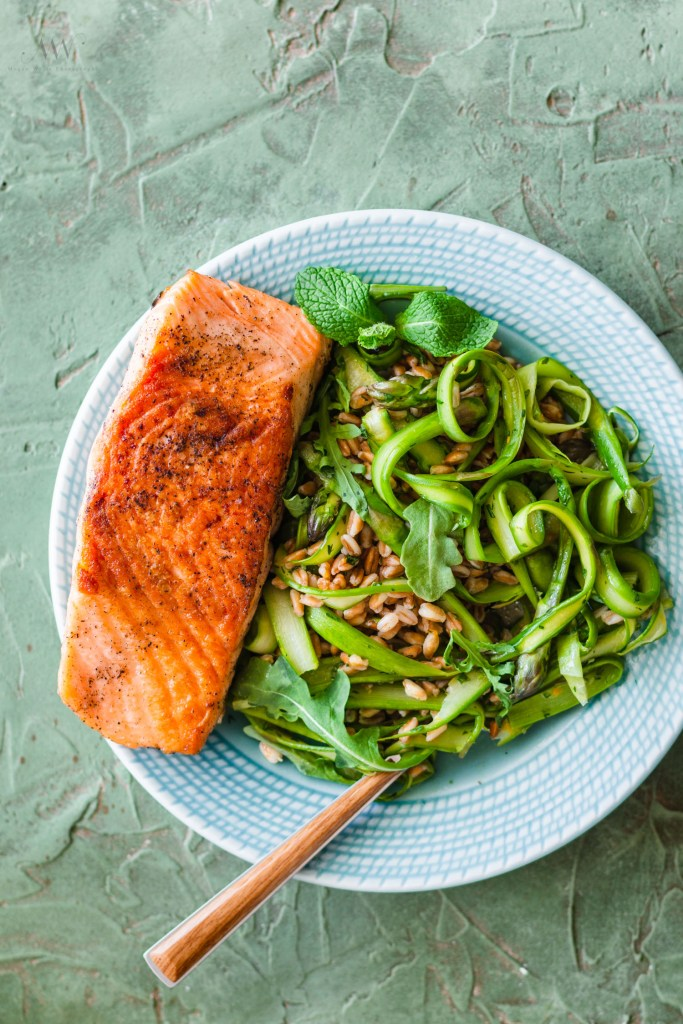 Overhead shot of a plate topped with farro, asparagus ribbons, arugula, and a salmon fillet with a piece of silver ware sticking out to the side.