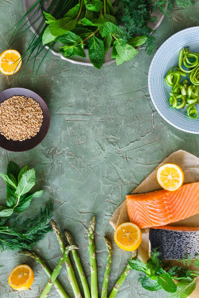 Overhead shot with empty space in the center and salmon, farro, fresh herbs, asparagus, and lemons arranged around the edges.