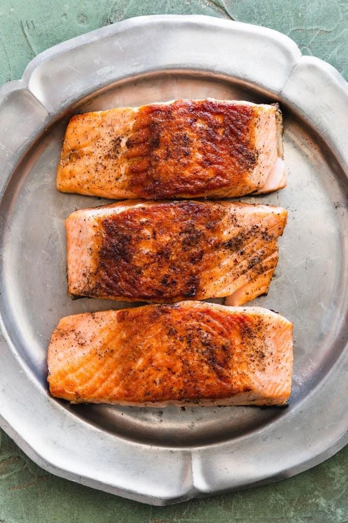 Overhead shot of three pan seared salmon fillets skin side down on a silver platter.