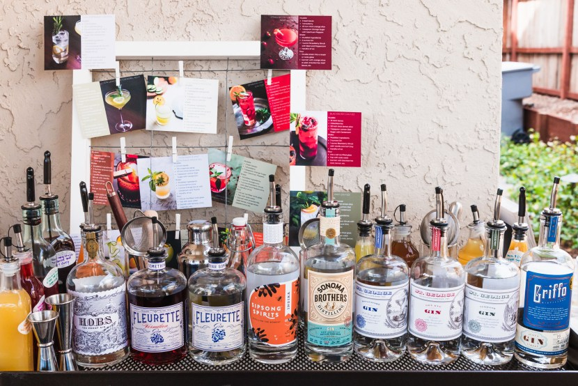 Side shot of gin bottles lined up on a bar surrounded by shrubs, syrups, bar tools, and recipe cards.