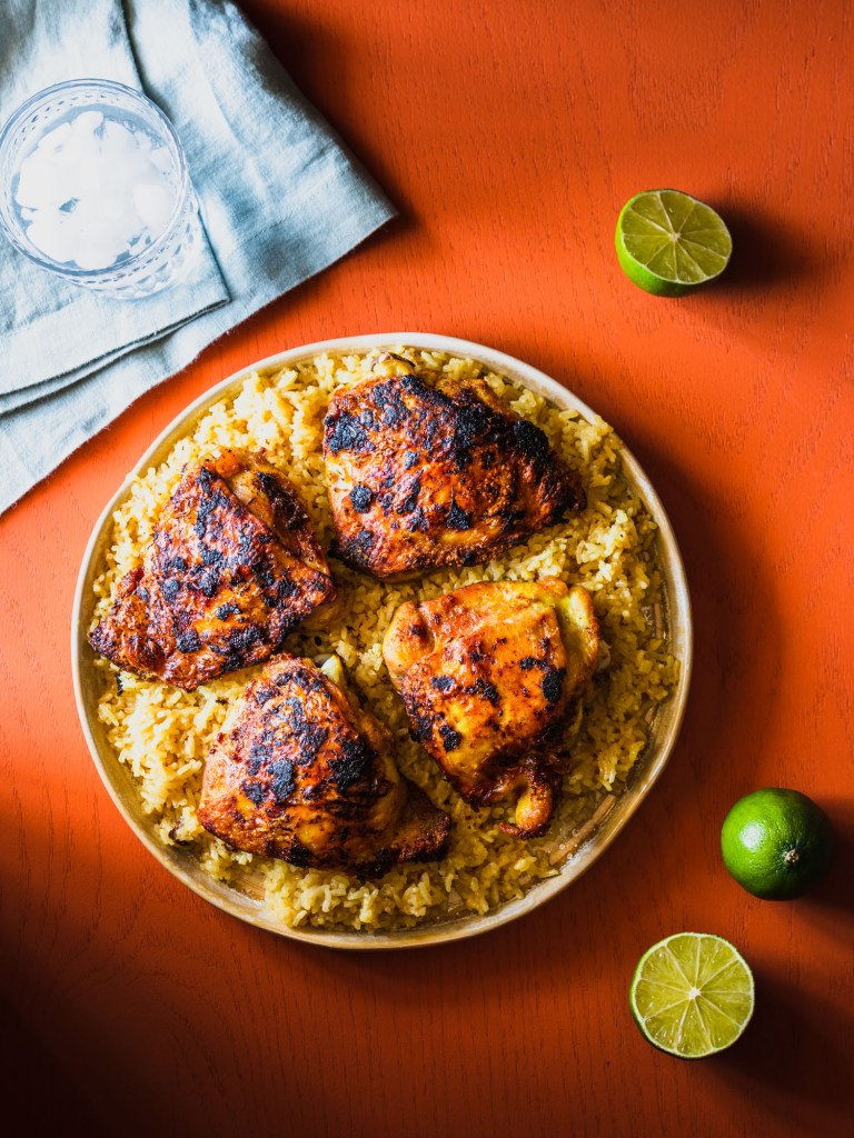 Overhead shot of a platter filled with rice and topped with chicken thighs surrounded by limes, folded napkin, and a glass of water.