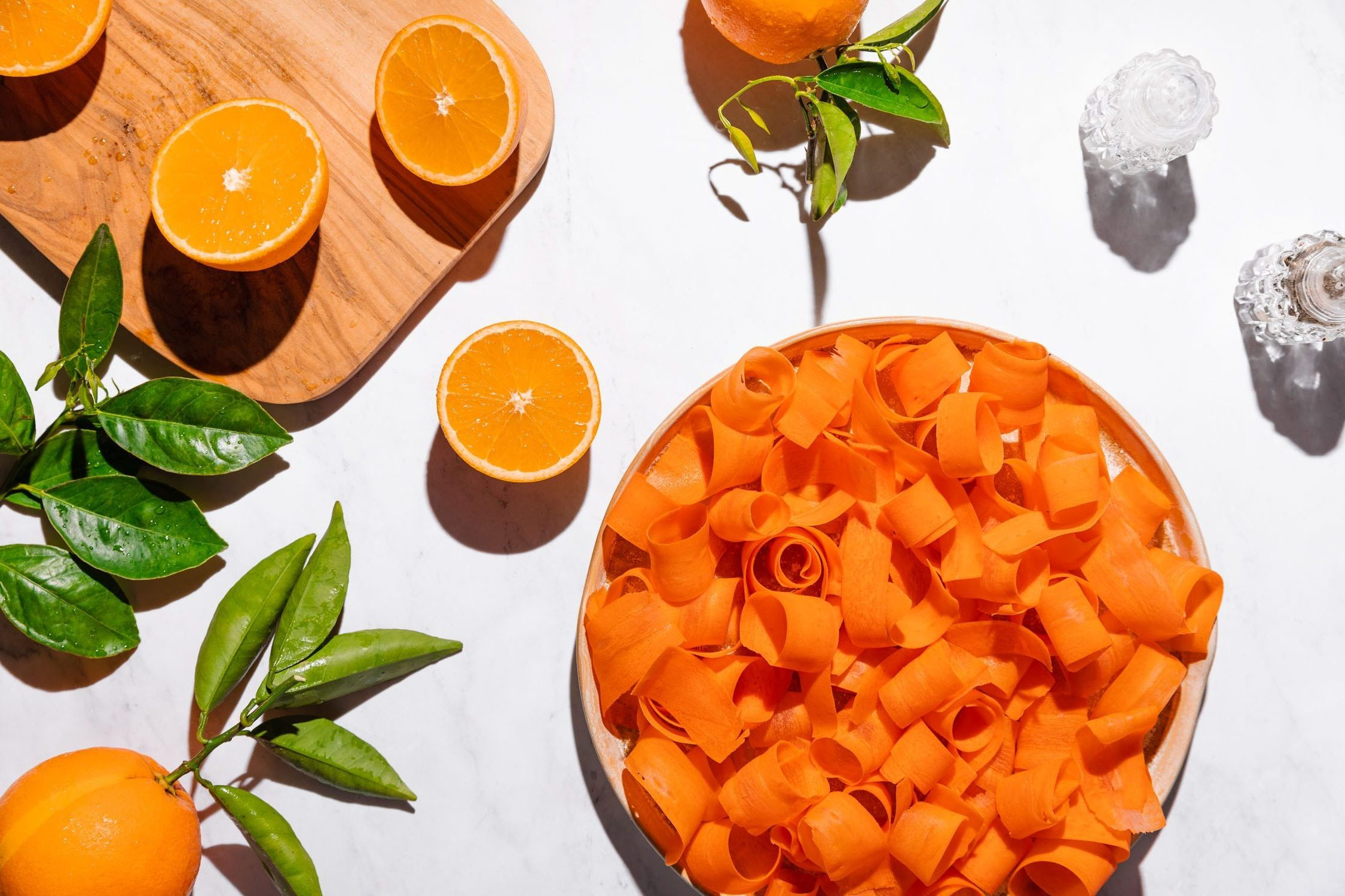Overhead shot of a plate filled with peeled and curled carrots surrounded by oranges and a cutting board.