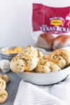 Make these simple, delicious, cheese stuffed Garlic Knots using Rhodes Bake-N-Serv Texas rolls for your next holiday dinner. Simple to make and taste homemade! Check out the step-by-step tutorial for these super simple rolls.