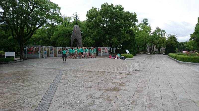 欧米の学生が千羽鶴の前で 整列、そして、おしゃべり。