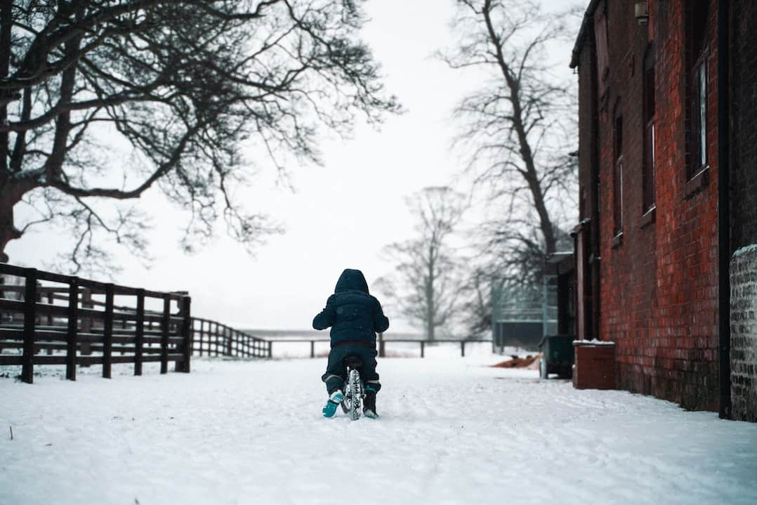 Child on bike in snow
