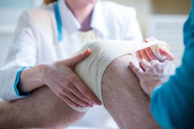 Sanitaria aplicando un vendaje en la rodilla.