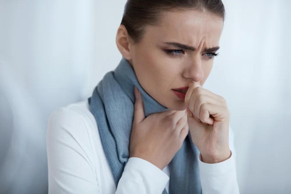 Mujer tosiendo con una bufanda en la garganta.