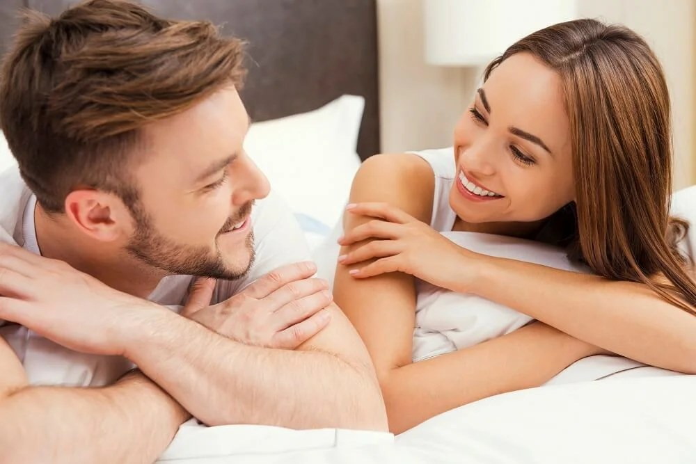Enjoying time together. Beautiful young loving couple lying in bed together and looking at each other with smile