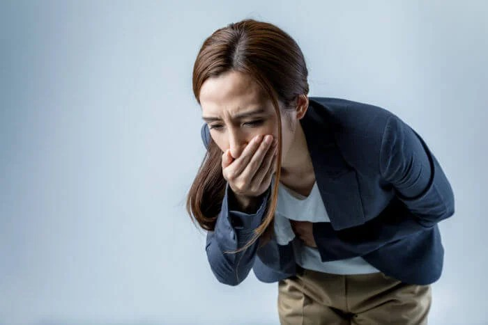 Mujer con cara de vomitar.
