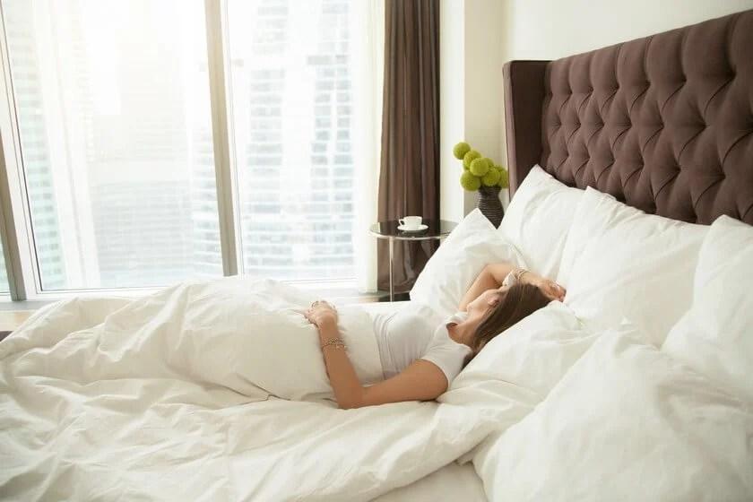 Mujer durmiendo boca arriba en un colchón duro