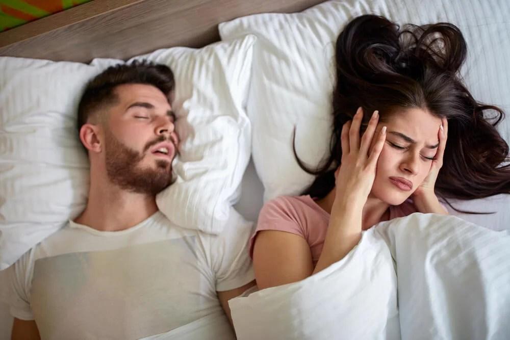 Mujer tapándose los oídos en la cama ante los ronquidos de la pareja.