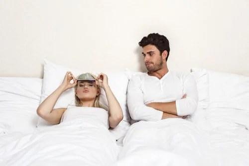 Pareja en la cama. Mujer preparada para dormir, hombre despierto.