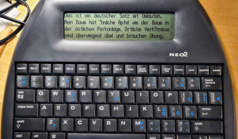 Ein Alphasmart Neo2 - Tastatur mit LCD-Display auf dem ein paar Zeilen Blindtext zu lesen sind. Das statt des ä steht im Text ein '