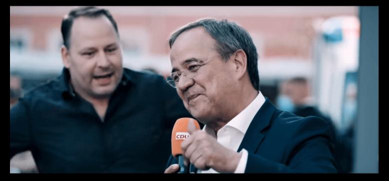 Screenshot des CDU-Wahlwerbevideos. Man sieht den Querdenker Thomas Brauner auf die Bühne laufen, während Laschet joival ins Publikum lächelt.