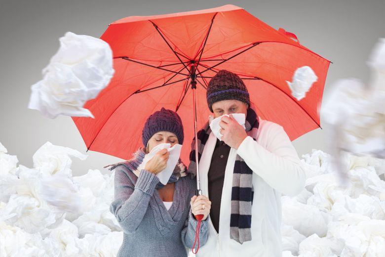 Mature couple blowing their noses under umbrela @ Wavebreakmedia