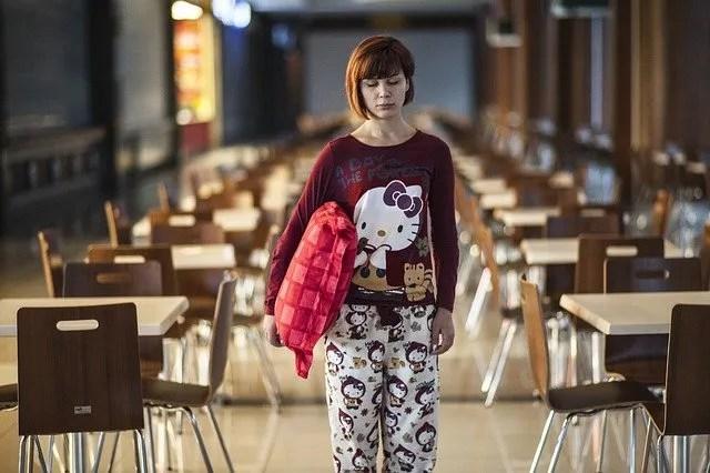 Una ragazza che cammina con cuscino alla mano verso la cucina.