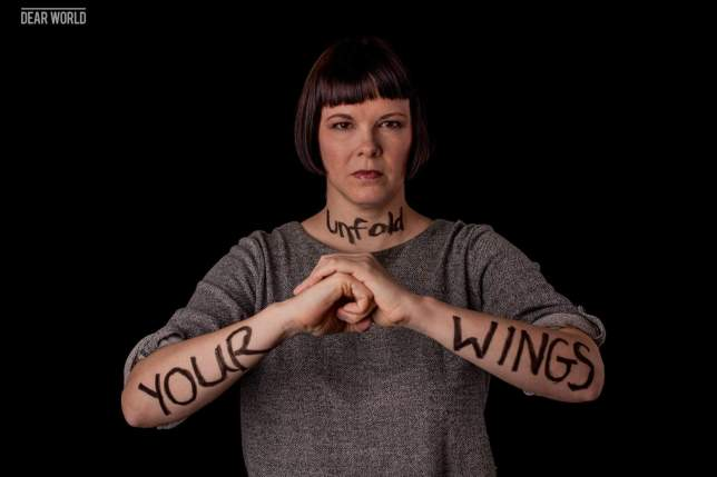"woman with ""unfold your wings"" written on her arms"