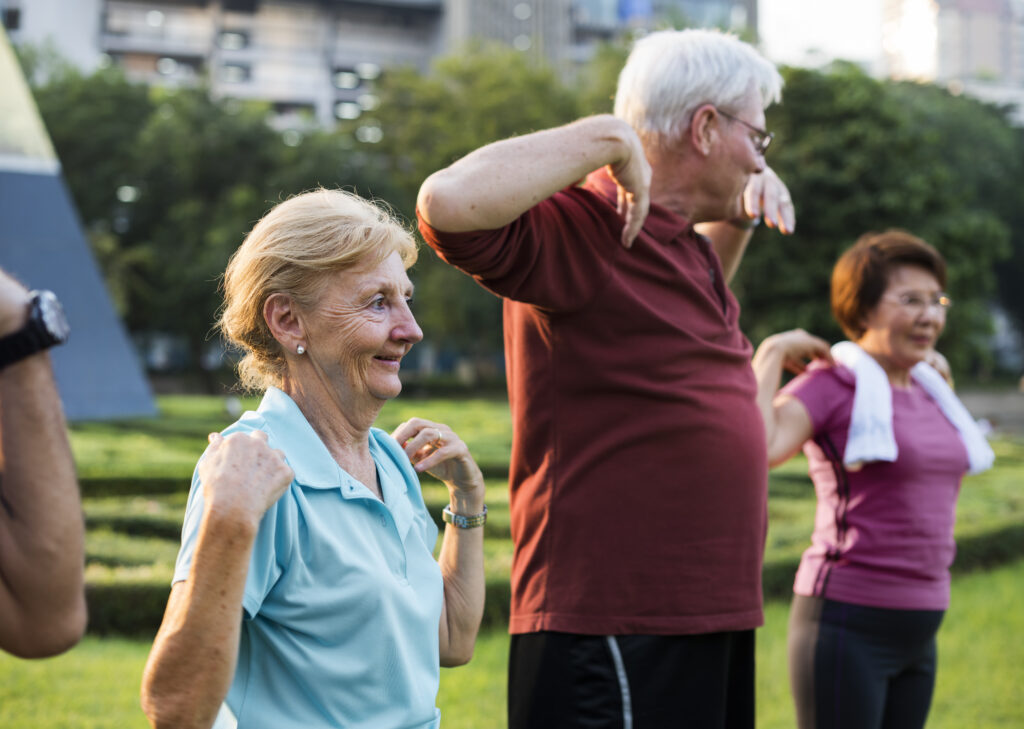 group exercise three older adults in a row each touching their own shoulders