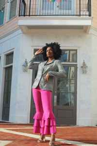 woman in gray long sleeve shirt and pink pants standing in front of white concrete building