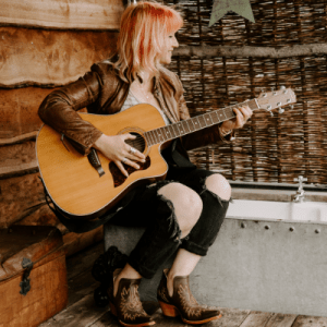 Pink hair and guitar country music leather jacket and cowboy boots