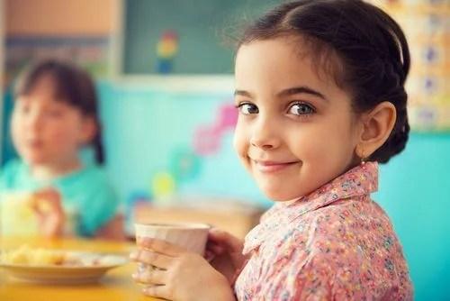 Menina sorrindo e comendo