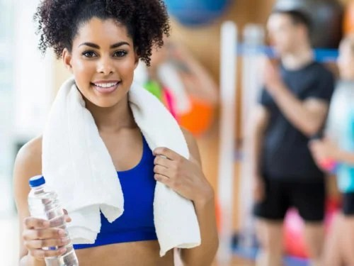 Mulher na academia com toalha e garrafa d'água
