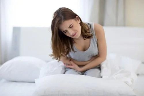 Mulher sentindo dor no abdômen