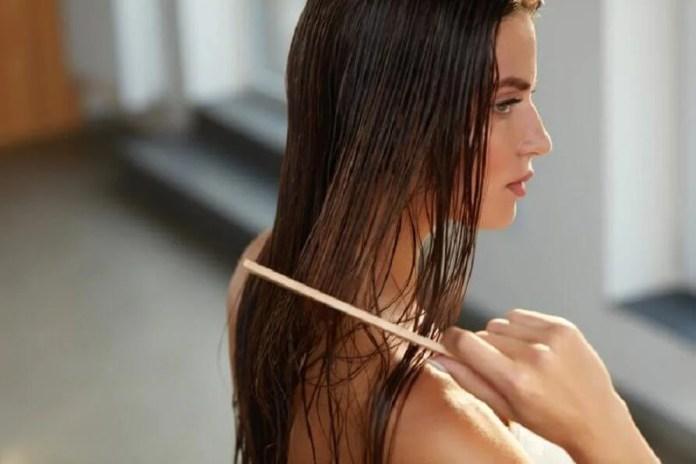 Mulher penteando cabelo molhado