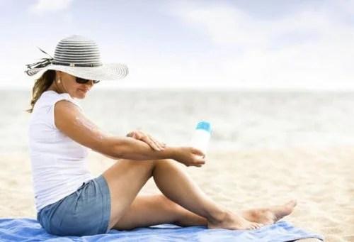 Mulher colocando protetor solar para evitar queimadura de sol