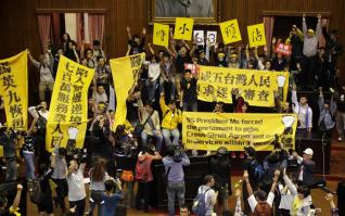 Students and other protesters hold banners inside Taiwan's legislature in Taipei