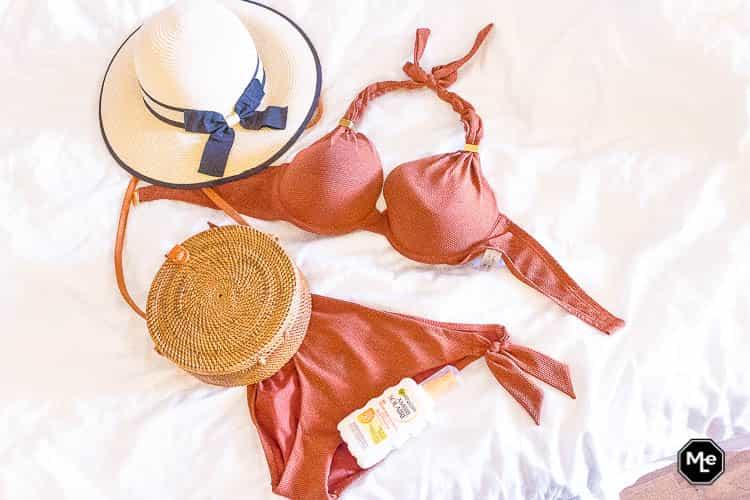 flatlay - rotan tasje bali, bikini, zonnebrand en zonnehoed