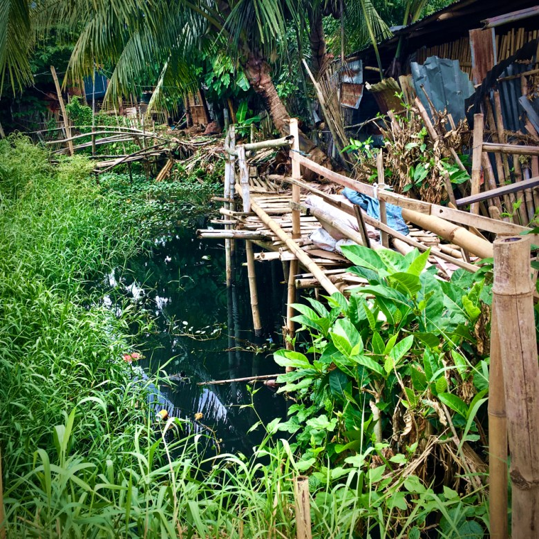 a tangle of makeshift bamboo walkways sit next to a massive shopping centre (Balasan) Philippines by Melinda J. Irvine