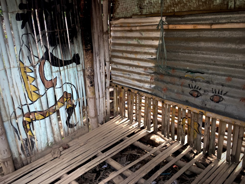dilapidated bamboo shack with street art type motifs