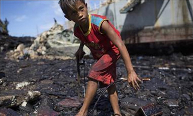 boy looking for scrap metal amidst an oil spill in the Philippines