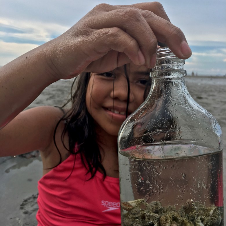 Filipino girl at the beach with a bottle of shells