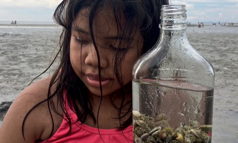 Filipino girl with a bottle of shells