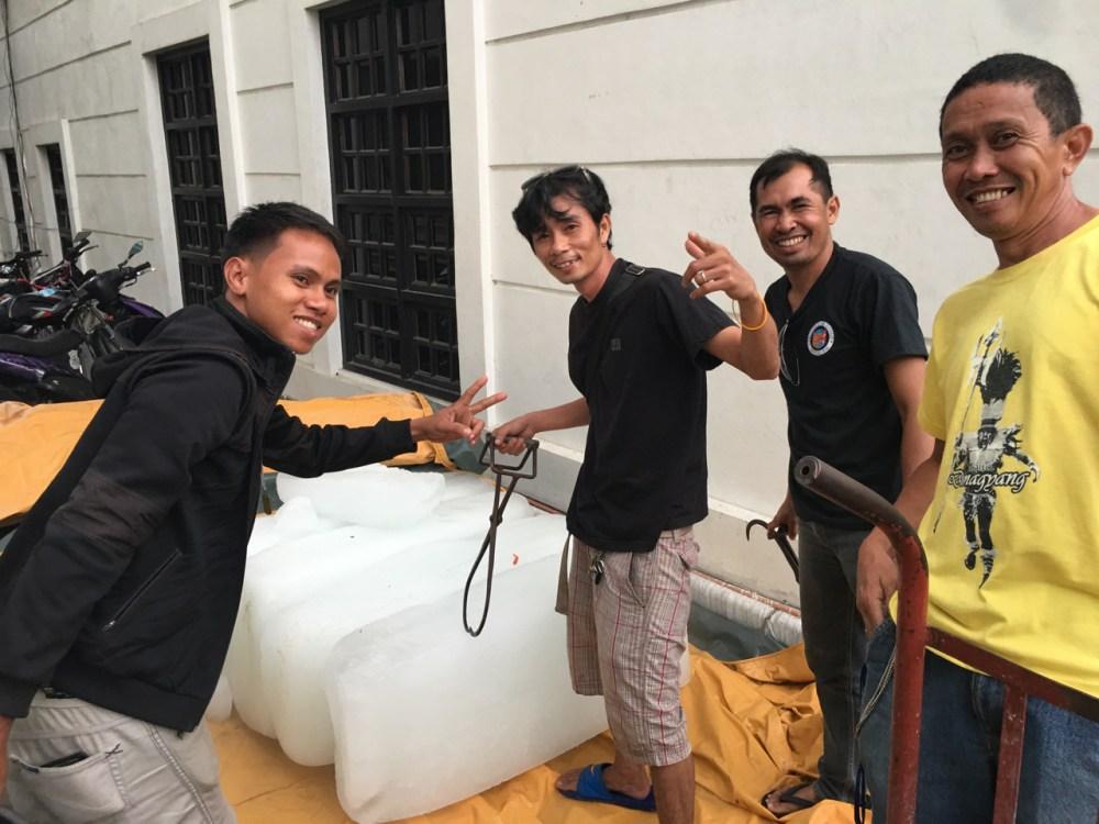 group of men handling large block ice