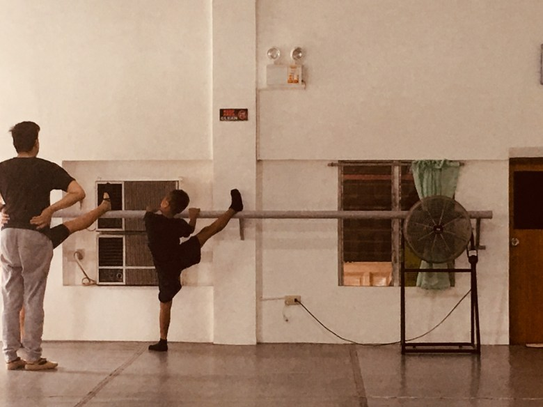 boy at the barre stretching