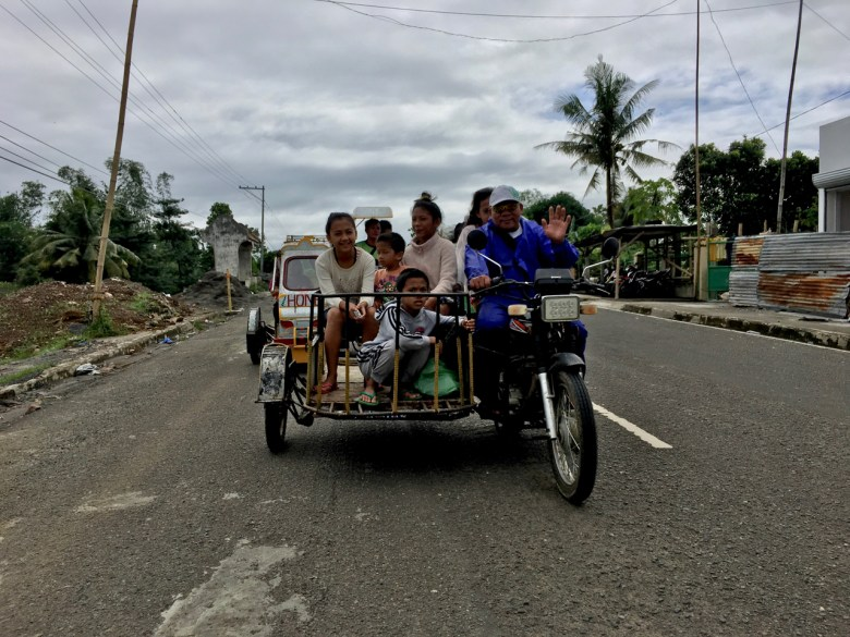 family riding a motorcycle and trailer to Balasan