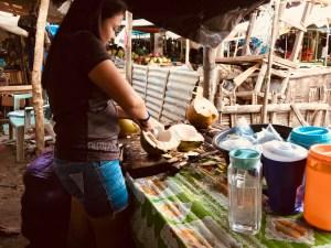 girl cutting coconuts