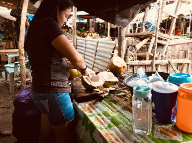 girl cutting coconuts
