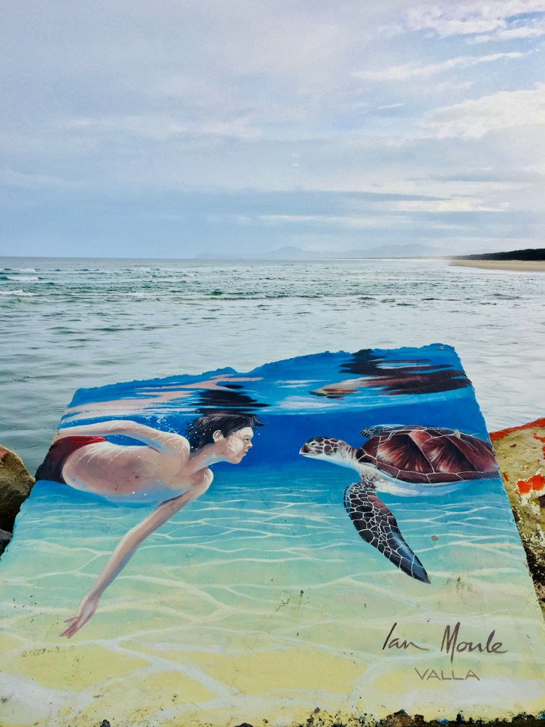 mural of a boy swimming with a sea turtle