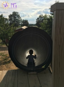 toddler boy in a tunnel slide