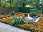 Orange zinnas and red cannas around one of the fountain areas.